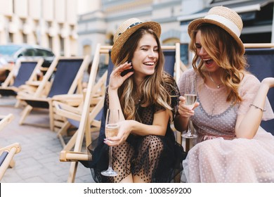Irresistible laughing girl listening friend's joke and drink champagne. Two stunning women spending time together and recollect funny stories while sitting outdoor with goblets.