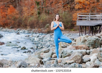 Irresistible positive young slim female yoga instructor stands in Vrikshasana pose against background of wild autumn nature. Concept of enjoying silence and nourishing natural energy. Place for text