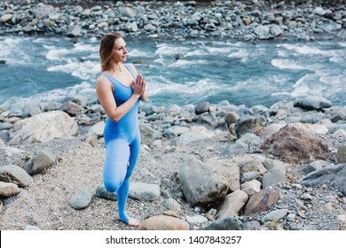 Irresistible positive young slim girl yoga instructor stands in Vrikshasana pose against background of wild autumn nature. Concept of enjoying silence and nourishing natural energy. Place for text