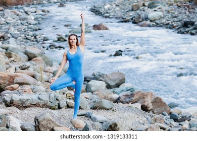 Irresistible positive young slim woman yoga instructor stands in Vrikshasana pose against background of wild autumn nature. Concept of enjoying silence and nourishing natural energy. Place for text