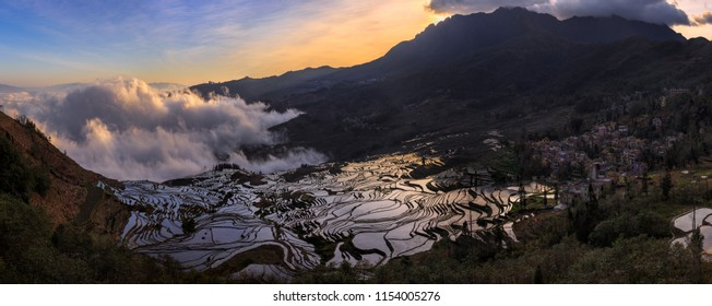 Irrigated Rice Terrace Fields in Yuanyang County - Yunnan Province, China. Water filled terraces, reflecting and absorbing the blue color of the sky. Duoyishu Sunrise panoramic view, sea of clouds