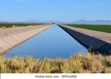 Irrigation canal between agricultural crops in California.