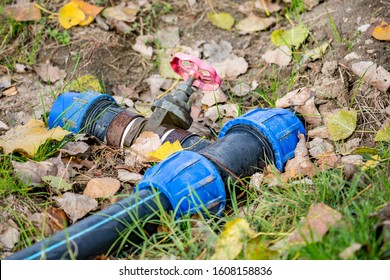 Irrigation equipment, autumn ground with brown foliage, blue connections of black cold-water pipe and rusty faucet with red handle, close-up against soil background. Zlato Pole, Bulgaria, Europe - Shutterstock ID 1608158836