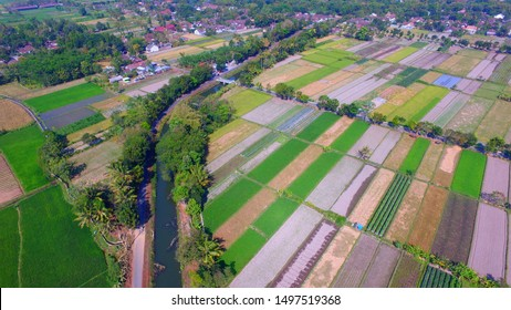 irrigation system for agriculture area. irrigation flow in the fields. Aerial agriculture from above with a drone camera in Asia and Indonesia.