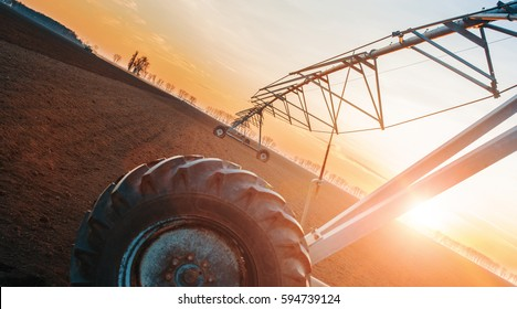 Irrigation system on the field at spring sunset. Agricultural concept