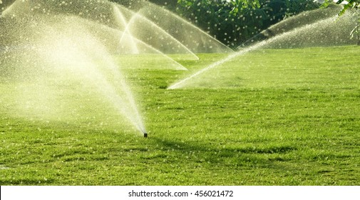 Irrigation System Watering the green grass with bokeh background
