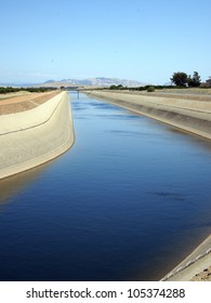 Irrigation water flows in a canal near an orange grove.