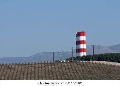 An irrigation water tower overlooks vineyards and orange groves in Central California