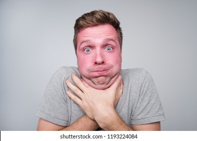 Irritatated fed up caucasian man making suicide gesture, tries to choke himself, being annoyed. He lost importnant competition or made a failure. His face is toned in red color