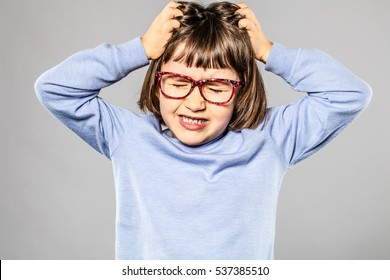irritated 6-year old young girl with eyeglasses pulling out her hair for itchy allergies or lice or scratching her head for nervous disagreement, grey background