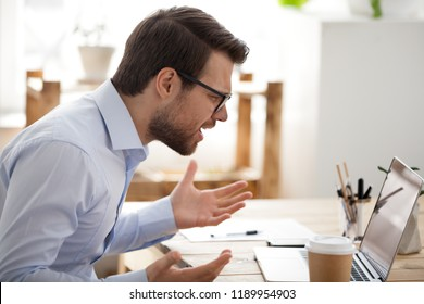 Irritated angry man sitting at the desk in office looking at laptop screen having problem, bad news. Side view of stressed, businessman noticed the error, failed to work, failure in business concept