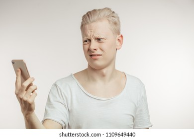 Irritated attractive male gestures with irritation, frowns face as recieves unpleasant message, clenches teeth, looks in mobile phone, isolated over white background.