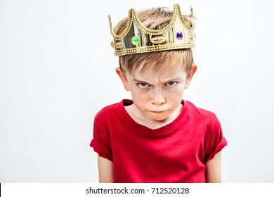 irritated beautiful spoiled boy with frowning freckles and a dirty look wearing a golden crown for mad attitude facing parenthood and education, white background, indoors