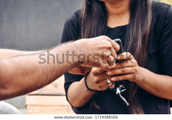 Irritated boyfriend pulls smartphone from girlfriend's hands, annoyed with his technology addiction, demands attention and care