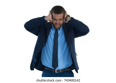 Irritated businessman covering his ears against white background