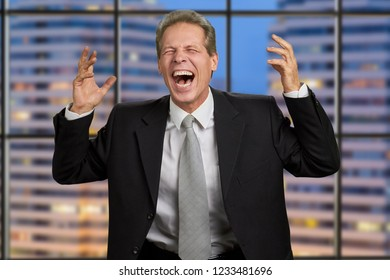 Irritated businessman with raised arms. Middle-aged businessman laughing hysterically with outstretched hands.
