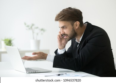 Irritated businessman talking over phone, working at laptop, solving company business problem, arguing. Angry manager speaking to technical support asking about computer or software malfunction