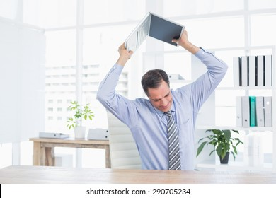 Irritated businessman trying to broke his laptop in his office