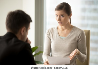 Irritated businesswoman holding paper, disagrees with bad contract terms, refuses to sign document, has questions claims to agreement conditions, boss dissatisfied with report or written work result