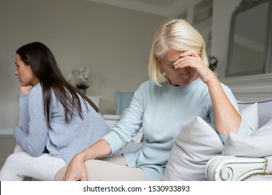 Irritated by quarrel upset young woman and mature unhappy mother sitting separately on cozy couch at home, ignoring each other. Depressed 2 generations family suffering from misunderstanding gap.