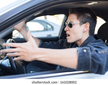 Irritated driver. Irritated young male driving a car