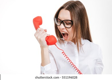 Irritated furious young business woman shouting at retro telephone tube over white background