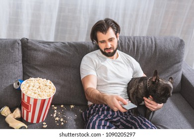 irritated loner watching tv with with bulldog on sofa in living room