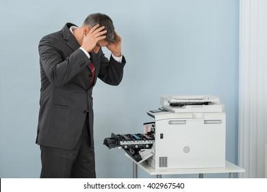 Irritated Mature Businessman Looking At Printer Machine At Office