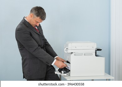 Irritated Mature Businessman Removing Paper Stuck In Printer At Office