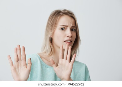Irritated scared blonde young female with straight fair hair in blue sweater posing against studio wall, keeping hands in stop gesture, trying to defend herself, saying: Stop that. Body language.