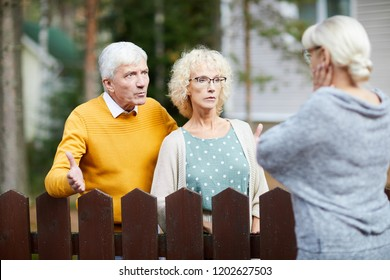 Irritated senior couple discussing trouble with their neighbour behind wooden fence