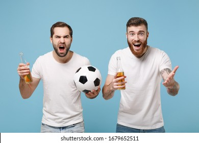 Irritated shocked two men guys friends in white t-shirt isolated on pastel blue background. Sport leisure concept. Cheer up support favorite team with soccer ball, beer bottle pointing hand on camera