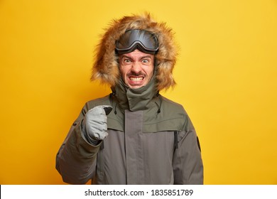 Irritated snowboarder clenches teeth from anger spends winter vacation in mountains clenches fist wears jacket and gloves displeased by cold weather isolated on yellow background. Resort recreation