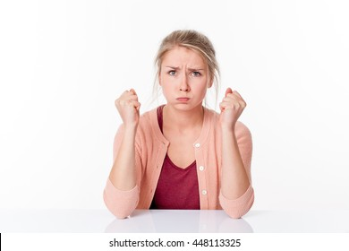 irritated young blond woman expressing herself with nervous fists up, puffing out her cheeks for exasperation over a white office background