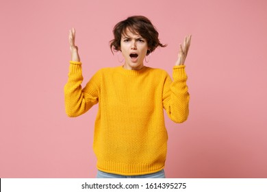 Irritated young brunette woman girl in yellow sweater posing isolated on pink wall background, studio portrait. People sincere emotions lifestyle concept. Mock up copy space. Swearing spreading hands