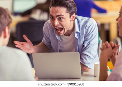 Irritated young man is using a laptop and screaming while working with other freelancers in cafe