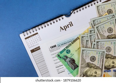 IRS 1040 tax return form with currency US dollar banknotes close-up stimulus economic tax return check