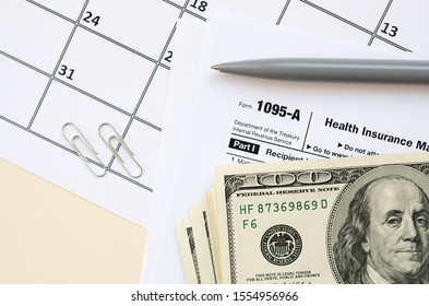 IRS Form 1095-A Health Insurance Marketplace Statement tax blank lies with pen and many hundred dollar bills on calendar page
