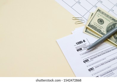 IRS Form 1095-B Health Coverage tax blank lies with pen and many hundred dollar bills on calendar page