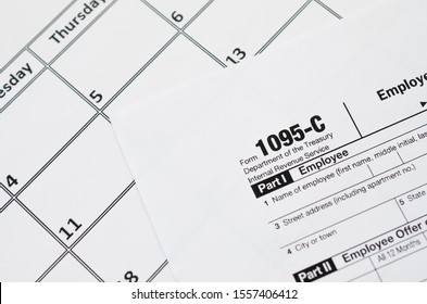 IRS Form 1095-C Employer-Provided Health Insurance Offer and Coverage tax blank lies on empty calendar page