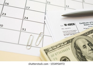 IRS Form W-8BEN Certificate of foreign status of beneficial owner for United States tax withholding and reporting for individuals blank lies with pen and hundred dollar bills on calendar page