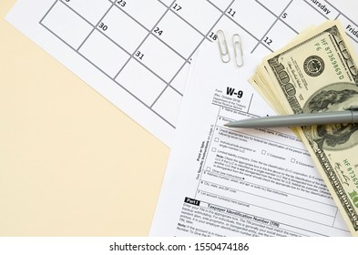 IRS Form W-9 Request for taxpayer identification number and certification blank lies with pen and many hundred dollar bills on calendar page
