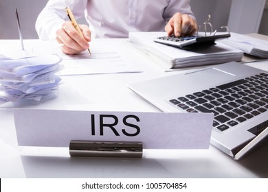 IRS Nameplate In Front Of Accountant Calculating Tax On Desk With Calculator And Laptop
