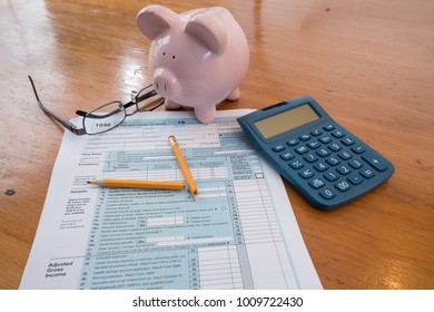 IRS Tax Form with Piggy Bank, Calculator, Broken Pencil and Glasses