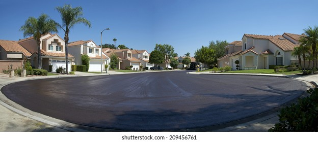 IRVINE, CA - AUGUST 06, 2014: Irvine's residential street rehabilitation and slurry seal project finished with crews expertly applying the slurry seal. Re-surfaced Cul-de-sac shown with crew departing