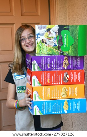 IRVINE, CA - JANUARY 07, 2014: Girl Scout Cadette at door with large Girl Scout Cookie boxes. Girl Scout Cookie Sales help girls learn marketing and money management skills.
