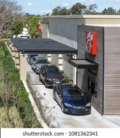 Irvine, CA, USA - April 16, 2018: Cars lined up at the drive thru window of Chick-fil-A, a fast food chain restaurant that makes chicken sandwiches their specialty.