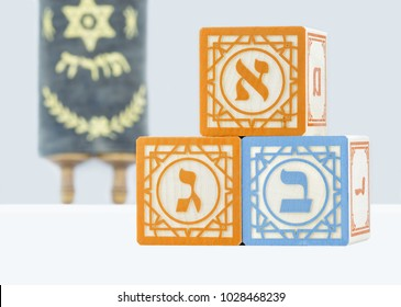 Irvine, CA, USA - February 13, 2018: Three Hebrew alphabet blocks with letters alef, bet, gimel on front faces on white surface. Letters dalet and mem on the sides. Small Torah in blurred background.