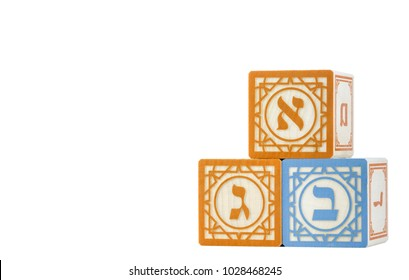 Irvine, CA, USA - February 13, 2018: Three Hebrew alphabet blocks with letters alef, bet, gimel on front faces isolated on white.  Letters dalet, mem on sides. Room for text. Jewish education concept.