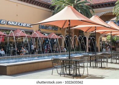 Irvine, CA, USA - January 29, 2018: Umbrellas, tables, chairs, and decorative water fountain at Irvine Spectrum Center outdoor shopping mall. People relaxing in the background.